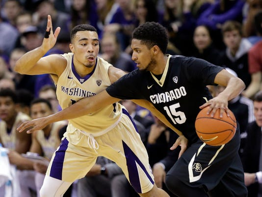 Washington's Andrew Andrews, left, fouls Colorado's Dominique Collier in the first half of an NCAA college basketball game Wednesday, Jan. 20, 2016, in Seattle. (AP Photo/Elaine Thompson)