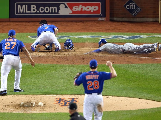 Royals' Eric Hosmer (35) scores the tying run past Mets catcher Travis d'Arnaud (7) in the 9th inning in Game 5 of the 2015 World Series at Citi Field.