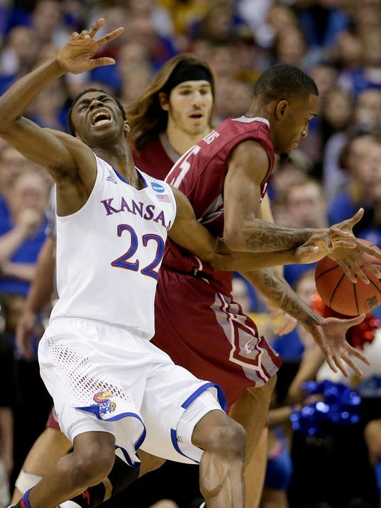 Kansas' Andrew Wiggins (22) and Eastern Kentucky's Orlando Williams chase a loose ball during the second half of a second-round game in the NCAA college basketball tournament, Friday, March 21, 2014, in St. Louis. Kansas won the game 80-69. (AP Photo/Charlie Riedel)