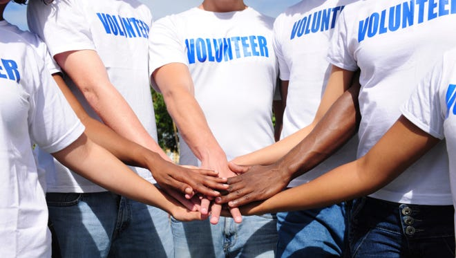 Volunteers bring their hands together.