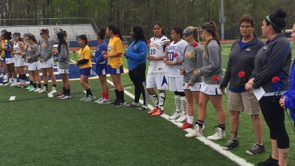 North Brunswick girls lacrosse players present red carnations to counterparts from Robbinsville