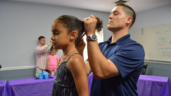 Dads learn to fix their girl's hair in a demonstration at Miller-Motte Technical College on Father's Day weekend.