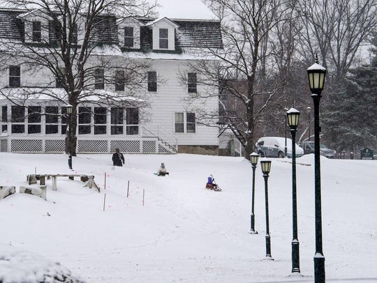 A family enjoys sledding on the Trinity Campus of the