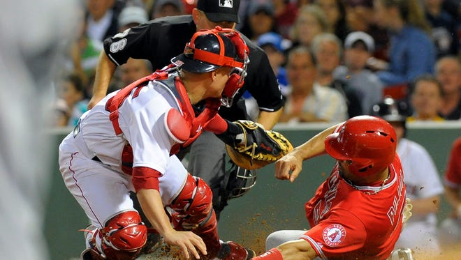 Boston Red Sox catcher Christian Vazquez (55) tags out Los Angeles Angels first baseman Albert Pujols (5) during the eighth inning at Fenway Park.