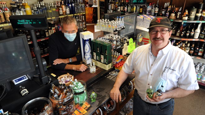 John's Liquor Store owner Mark Ferreira, right, pictured with head sales associate Peter Cvitan, palms a handful of nips in his store on Main Street in Falmouth. The store is one of several liquor establishments in Falmouth that stand to be affected by a ban on nip bottle sales that passed at town meeting on Monday.
