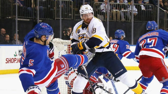 Dan Girardi (5) of the Rangers is checked by James Neal of the Predators during the first period.