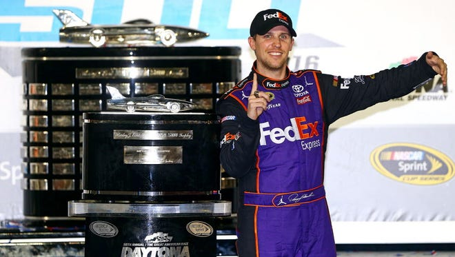 Denny Hamlin (11) poses with the Harley J. Earl Trophy after winning the Daytona 500 in 2016.
