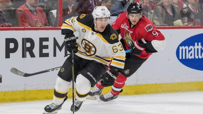 Boston Bruins left wing Brad Marchand (63) skates with the puck in front of Ottawa Senators right wing Bobby Ryan (9) in the second period.