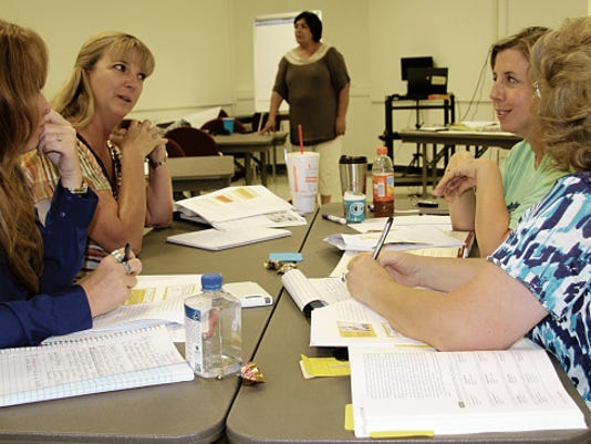 Trainer Sylvia Martinez, center, waits as teachers discuss effective review techniques Wednesday during their two-day training session.
