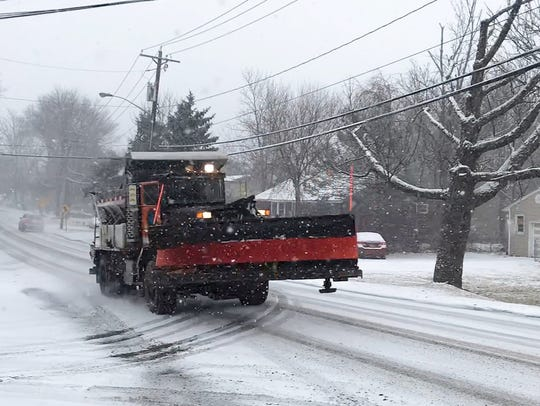A county snow plow spreads salt on Willow Grove Road