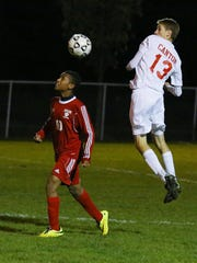 Kyle Mettlach (No. 13) of Canton keeps the ball in sight Wednesday night. At left for Grand Blanc is Omar Saeed.