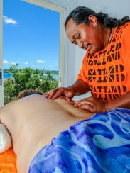 In this file photo, Festival of Pacific Arts Cook Islands delegation member Teuvira Upokotea demonstrates the art of healing through traditional massage in the Guma Yo' Amte, or House of the Healer, at the Sagan Kottura Chamoru cultural center in Tumon.