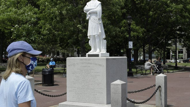 A passer-by walks near a damaged Christopher Columbus statue, Wednesday, June 10, 2020, in a waterfront park near the city's traditionally Italian North End neighborhood, in Boston. The statue was found beheaded Wednesday morning, Boston Mayor Marty Walsh said.