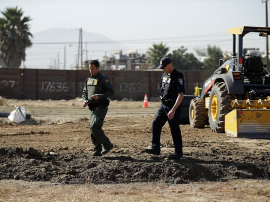 A Border Patrol agent walks with a Department of Homeland Security official as crews work on prototypes for a proposed border wall in front of the primary border structure separating Tijuana, Mexico, behind, and San Diego   on Sept. 27.