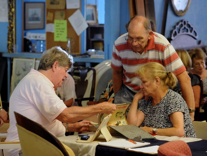 Dan and Joanne Gee get their 1030's bound Japanese magazines appraised by Winston Garth Saturday during the 19th annual Antique Appraisal Fair at Garth's Auction Gallery. Proceeds help keep the nonprofit Quina House Museum open at no charge to visitors.