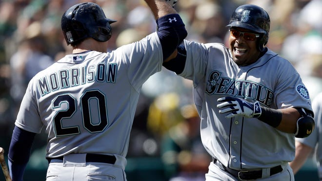 Seattle Mariners' Nelson Cruz, right, is congratulated by teammate Logan Morrison (20) after hitting a three-run home run in the eighth inning of a baseball game against the Oakland Athletics, Saturday, April 11, 2015, in Oakland, Calif. (AP Photo/Ben Margot)