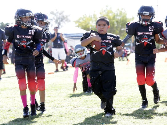Nine-year-old Emmanuel Dominguez runs for a touchdown