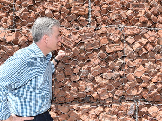 Property owner Karl Slovin admires a gabion wall made of Hutton bricks at the Hutton Brickyards in Kingston. The property is hosting two Bob Dylan concerts June 23-24.