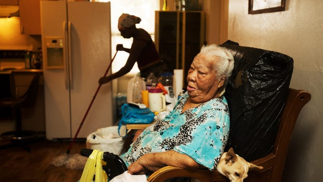 Charleston Park resident Carrie Spearman, sits in her home with her dog Chloe. On the left is Christal Bolden. She's one of several residents being helped with water treatment systems provided by Clean Water for Charleston Park.