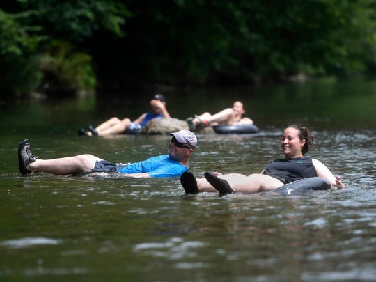 Rachel Coler, right, and Bill Coler of North Lima, Ohio, tube along Yellow Breeches Creek in Upper Allen Township. Tubers, kayakers and swimmers all mingle in this spot near the covered bridge on the Messiah College campus.