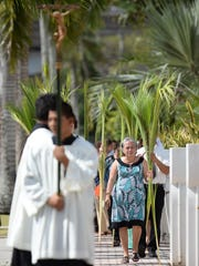 Church goers carry palm fronds on Palm Sunday to the