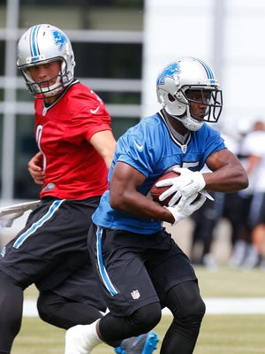 Detroit Lions quarterback Matthew Stafford, left, hands off to running back Theo Riddick during NFL football practice in Allen Park, Mich., Tuesday, June 14, 2016.
