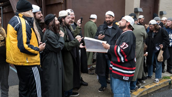 """Kevin Smith treats fans to doughnuts as they line up along Broad and Mechanic streets in Red Bank to set a Guinness world record for the largest gathering of Jays and Silent Bobs and celebrate the 20th anniversary of Jay and Silent Bob's Secret Stash Comic Book Store. AMC was filming the episode for """"Comic Book Men."""""""
