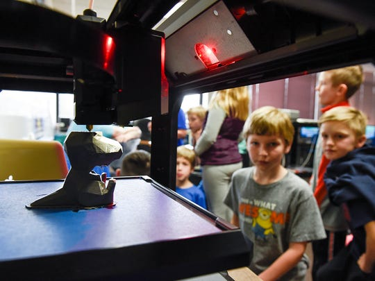 Students in third grade watch a 3-D printer create