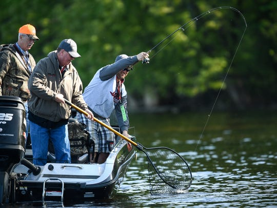 Anglers net a smallmouth bass during the 2017 Governor's Fishing Opener Saturday, April 13, on the Mississippi River in St. Cloud.