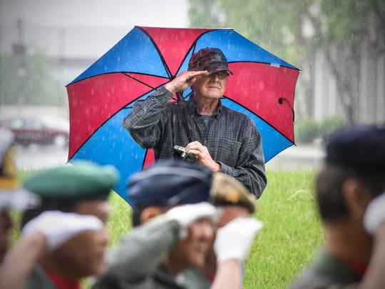 Veterans salute at the beginning of the Vietnamese