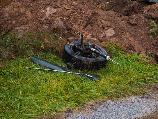 A wheel sits near a mound of dirt at the accident scene