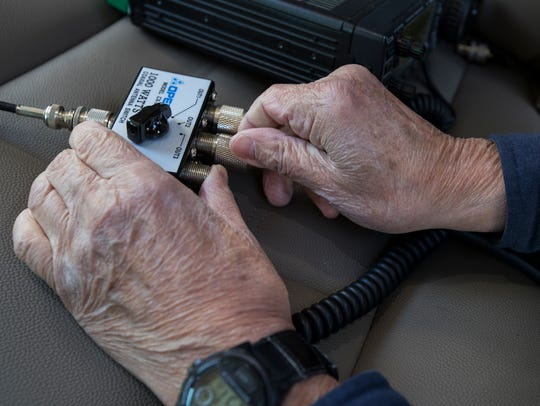 Joe Huie, 87, sets up his Ham radio antenna in an open