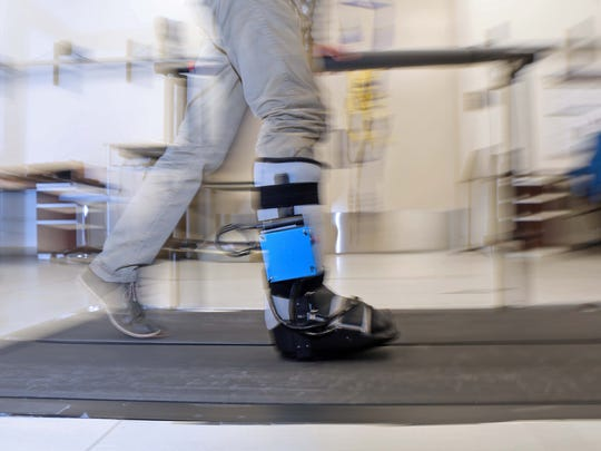Collin Patterson, a senior biomedical engineer at the University of Delaware demonstrates how the SmartBoot,  created by school researchers and students works by measuring overloading to limbs after surgery, by walking too soon or putting weight on their foot/leg.