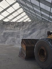 A front-end loader is positioned to transfer road salt