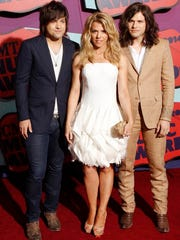 Neil Perry, from left, Kimberly Perry and Reid Perry of the musical group The Band Perry arrive at the CMT Music Awards at Bridgestone Arena on Wednesday, June 4, 2014, in Nashville, Tenn.