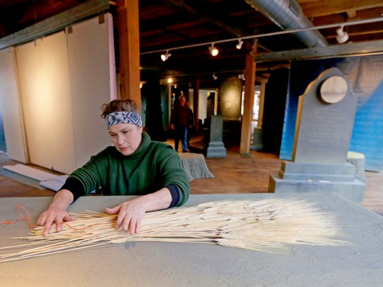"""Artist Terese Agnew arranges wheat reeds while installing """"Writing in Stone"""" at RedLine Gallery on N. 4th St. in Milwaukee."""