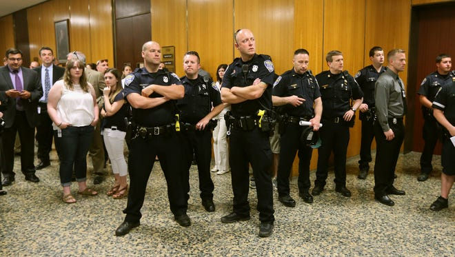 Rochester police officers crowd the hallway outside the courtroom where Thomas Johnson lll was found guilty of aggravated murder in the death of fellow officer Daryl Pierson.