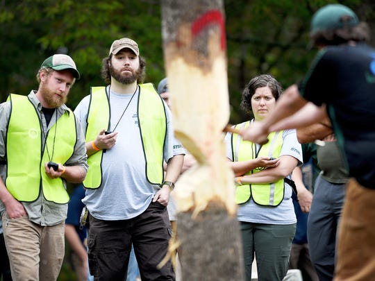 From left, Peter Simmons, Andrew Isenhower and Sarah Justice time the pole fell competition at the woodsmen's meet October 7, 2017.