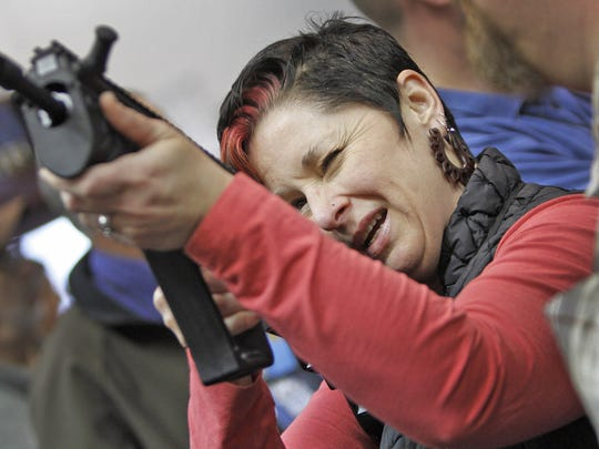 Sharon Hitzeroth, from Indianapolis, tries out a trigger on a gun during the NRA Convention at the Indiana Convention Center on April 25, 2014.