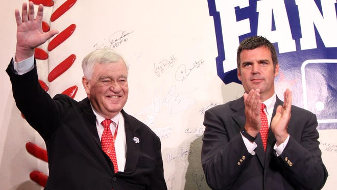 Reds CEO Robert Castellini, left, waves to the crowd at FanFest, the kickoff event for the All-Star Game. At right is his son, Phil Castellini, Reds COO.