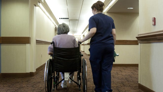 A resident is escorted down a hallway by a nurse's aide in Mason, Ohio.