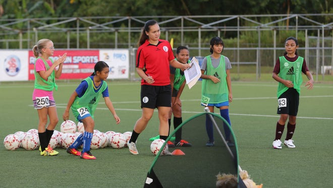 United Airlines GFA National Academy Girls U12 assistant coach Colleen Naden, in red, looks to send a pass to begin an activity during the Girls U12 open trial session for the annual program Thursday at the Guam Football Association National Training Center. The Academy, supported in large part by Japan Football Association, will include an additional division - the Girls U9 division - based on high turnout rates.