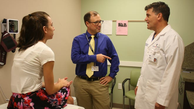 Stephen Lupe, a doctoral student in Florida Tech's Graduate Psychology Education Program, consults with Dr. Dan Strub, chief of internal medicine at Brevard Health Alliance, during a patient visit.