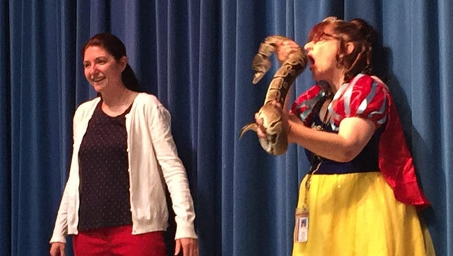 As part of a fundraiser for Lincoln County Humane Society, Hewitt-Texas Elementary School principal Cassie O'Keefe smooched a five-foot long python while dressed in a Snow White costume.