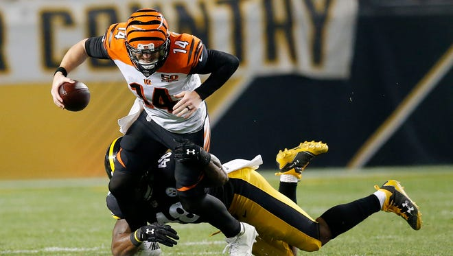 Cincinnati Bengals quarterback Andy Dalton (14) is sacked by Pittsburgh Steelers outside linebacker Bud Dupree (48) as he scrambles in the fourth quarter.