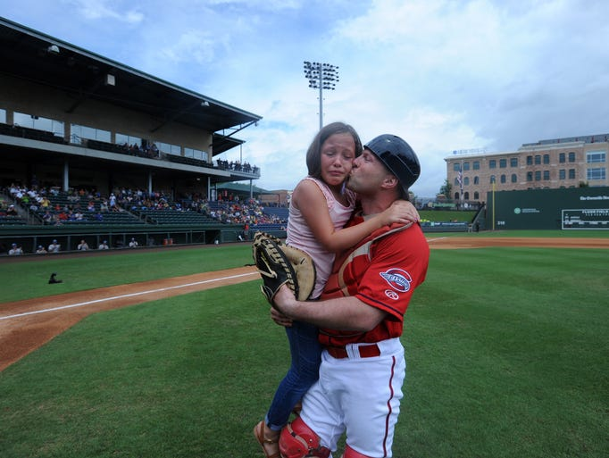 SSgt Michael Isbell, posing as a Greenville Drive catcher, surprises his daughter Cami Isbell after she throws the first pitch in Monday's game.  July 21, 2014.
