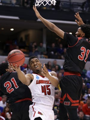 U of L's Donovan Mitchell (45) tried a tough shot against Jacksonville State's Malcolm Drumwright (21) and Christian Cunningham (31) during the NCAA tournament at the Bankers Life Fieldhouse in Indianapolis.Mar. 17, 2017