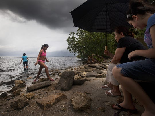 Maria Govea, second from right, watches granddaughter Alina Nunez, 9, second from left, and daughters Veronica, 11, left, and Crystal Govea, 13, as they dodge raindrops at the Tarpon Street Pier in east Fort Myers.