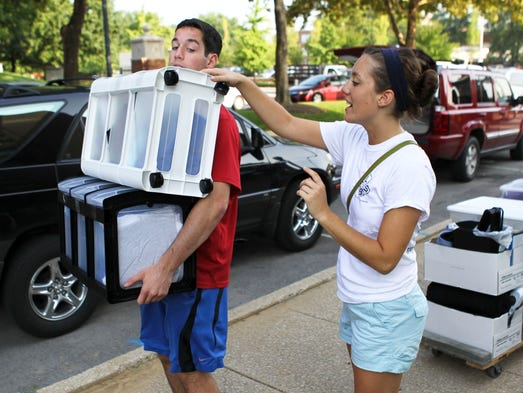 "Madeleine Loney, a senior at U of L, helps her brother Brian Loney load up his belongings as the freshman moves into Johnny Unitas Tower Wednesday morning. Loney said she was excited her younger brother is attending Louisville. ""I thought he might go to UK,"" she said. Aug. 20, 2014 By Matt Stone/The C-J"