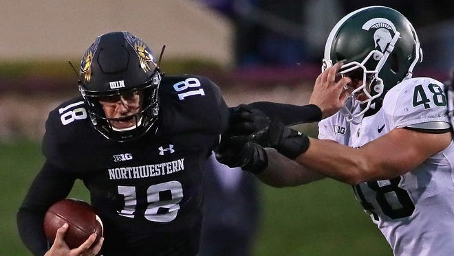 Clayton Thorson #18 of the Northwestern Wildcats holds off Kenny Willekes #48 of the Michigan State Spartans as he runs for yardage at Ryan Field on October 28, 2017 in Evanston, Illinois. Northwestern defeated Michigan State 39-31 in triple overtime.